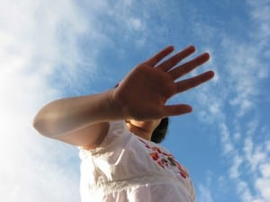 Hand Blocking Girl's Face with a Blue Sky Backdrop