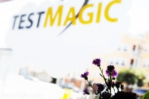 Blurry TestMagic window sign, with flowers in focus.
