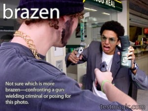 """Image of two males pointing guns at each other to illustrate the vocabulary word """"brazen""""."""